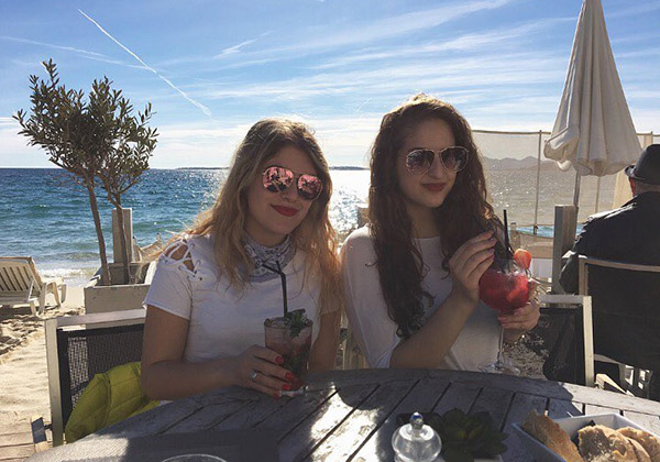 Victoria and her best friend enjoy summer drinks beside the ocean.